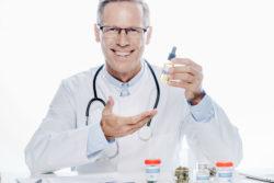 Médecin de sexe masculin mature détient un flacon d'huile de CBD