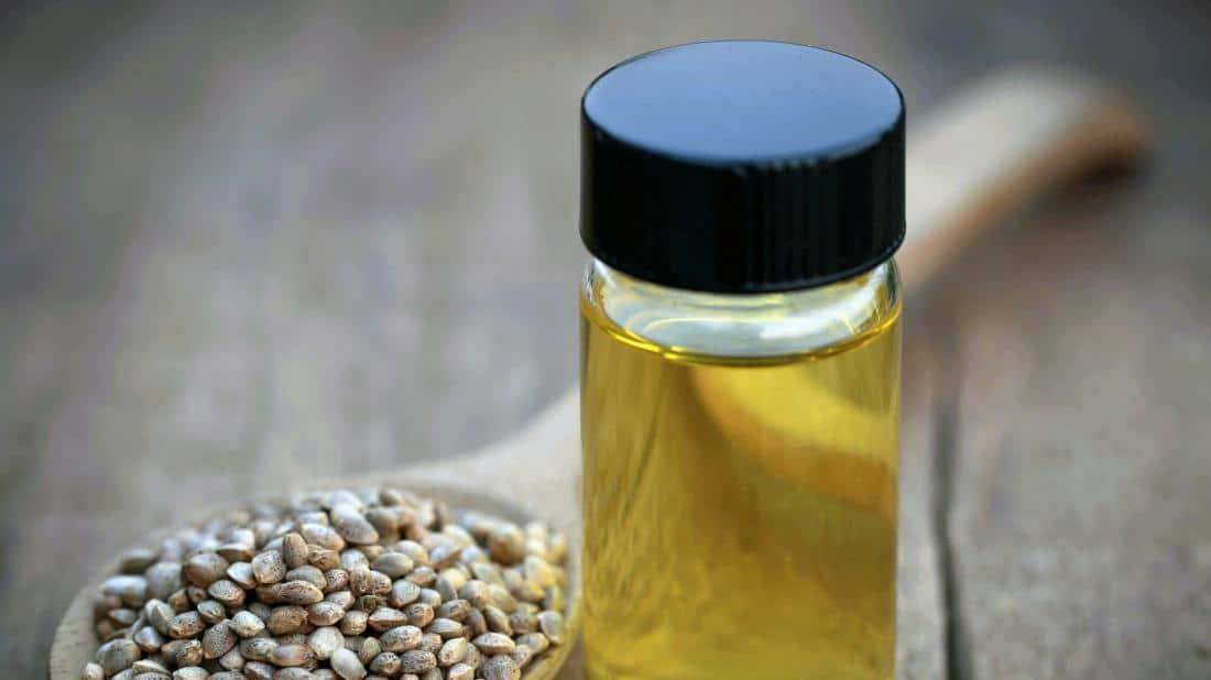 une bouteille d'huile de CBD à côté de quelques graines de chanvre